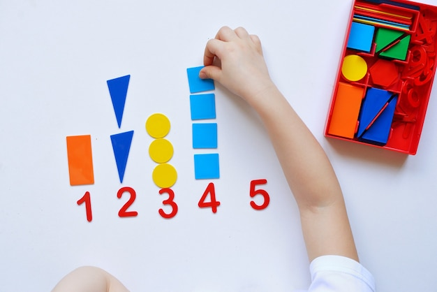 子供は数直線と幾何学的な形を学びます。未就学児はモンテッソーリ教材を使用しています。