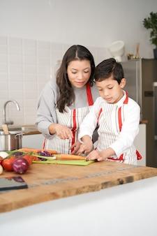 아이는 엄마가 라틴 사람들을 지켜보는 동안 야채 자르는 법을 배우고 그를 조심스럽게 도와줍니다.