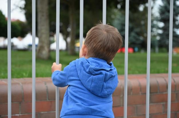 子供は金属フェンスを見ます。