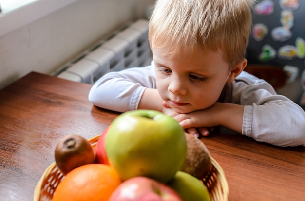 Ребенок ищет фрукты и улыбается.