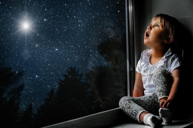Ребенок смотрит в окно в ночное небо