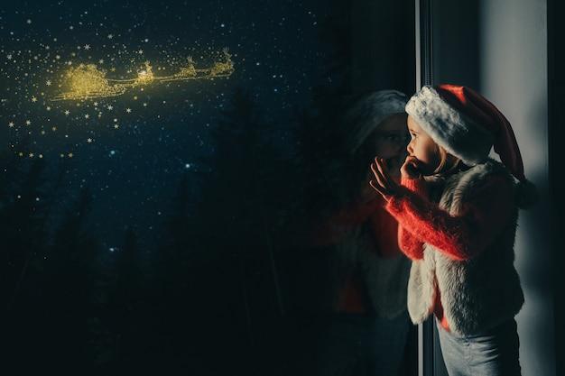 子供はクリスマスの日に窓の外を見ます