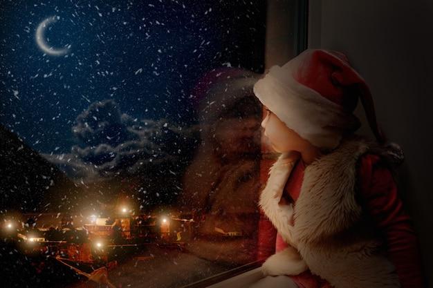 아이는 크리스마스 날 창밖을 내다본다