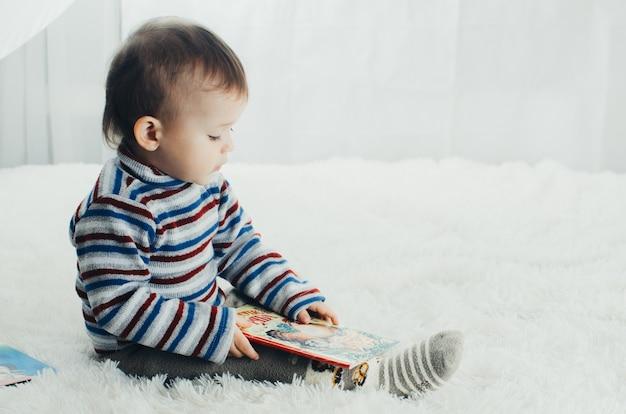 Ребенок смотрит в книгу, очень увлечен своим занятием, нравится