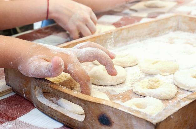 Ребенок проделывает пальцем дырочку для пончика. готовим дома. мастер-класс по приготовлению сладких пончиков.