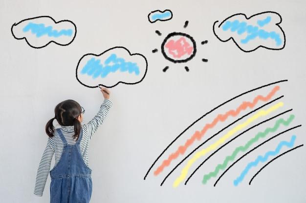 아이가 코로나바이러스 전염병 종식을 위한 희망의 상징으로 코로나바이러스로 인해 도입된 검역소 벽에 무지개를 그립니다. 무지개의 어린이 그림