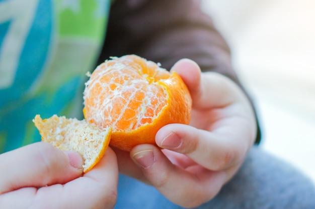 Ребенок снимает кожицу с мандарина, чтобы поесть. здоровое питание, новогоднее настроение