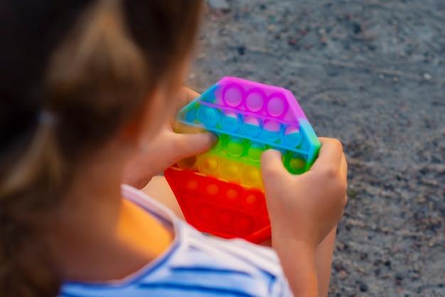 아이는 팝핏의 화려한 무지개 게임을 가지고 노는다. 실리콘 피젯 클로즈업입니다.