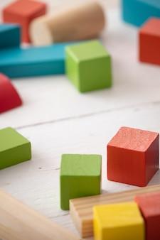 아이는 흰색 나무 탁자에 천연 나무로 만든 다채로운 기하학적 모양을 가지고 노는다