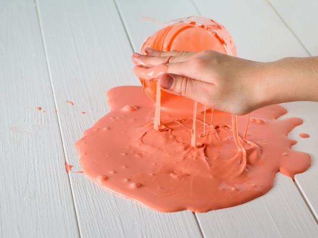 子供はテーブルオレンジのスライムにこぼれた手で遊ぶ。