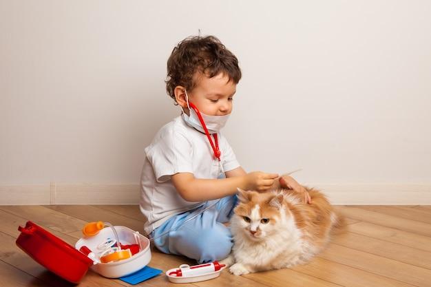 子供は医者の中でペットと遊んで注射をしようとします。