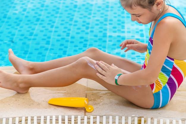 子供はプールのそばの彼女の足に日焼け止めを置きます