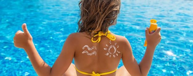 子供は背中に日焼け止めを置きます。セレクティブフォーカス。キッド。