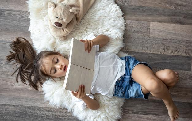 Ребенок читает книгу, лежа на уютном коврике дома со своим любимым игрушечным мишкой.