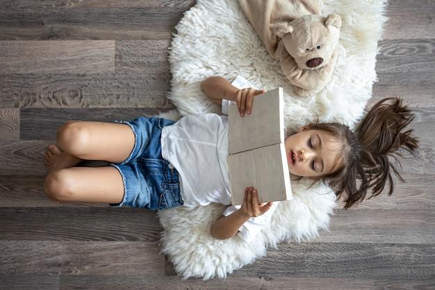 아이는 집에서 가장 좋아하는 장난감 테디베어와 함께 아늑한 깔개에 누워 책을 읽습니다.