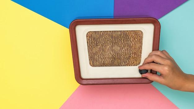 아이가 색이있는 표면에서 복고풍 라디오의 볼륨 조절기를 돌립니다.
