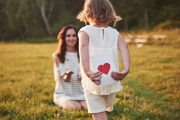 子供の娘は母親を祝福し、はがきを渡します。母と女は笑顔で抱きしめます。