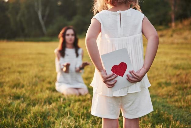 Дочь ребенка поздравляет маму и дарит ей открытку.