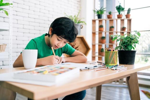 木製のテーブルに笑みを浮かべて白い紙に色鉛筆で子供の絵。幼稚園や小学校でアートを通して表現された子どもたちの創造性。学校に戻る。