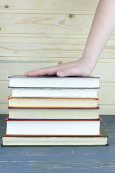 子供の手は木製のテーブルの上の本のスタックにあります