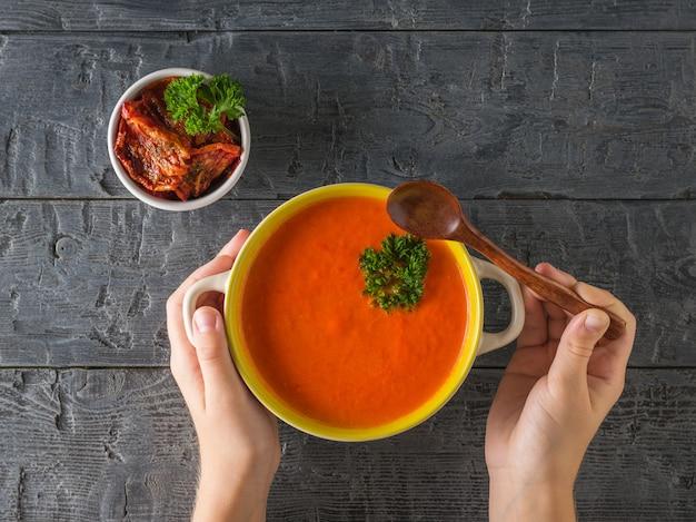 子供の手は木のスプーンとコショウのスープのクリームのプレートを持っています。菜食のスープ。フラットレイ。上からの眺め。