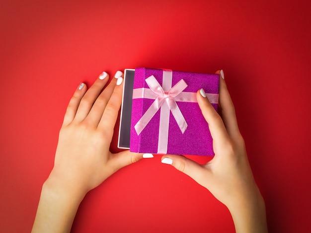 Руки ребенка открывают подарочную коробку на красном фоне. сюрприз в руках девушки.