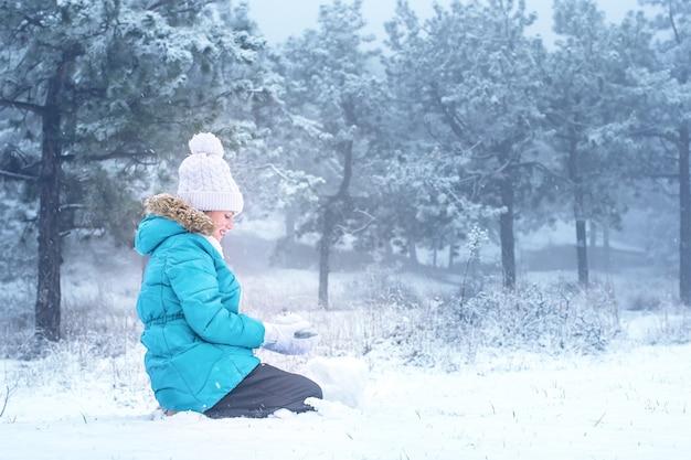 Ребенок лепит в лесу из снега. маленькая девочка в снегу. зимние забавы.