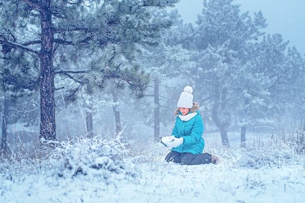 아이는 숲에서 눈으로 조각합니다. 눈 속의 소녀. 겨울 재미.