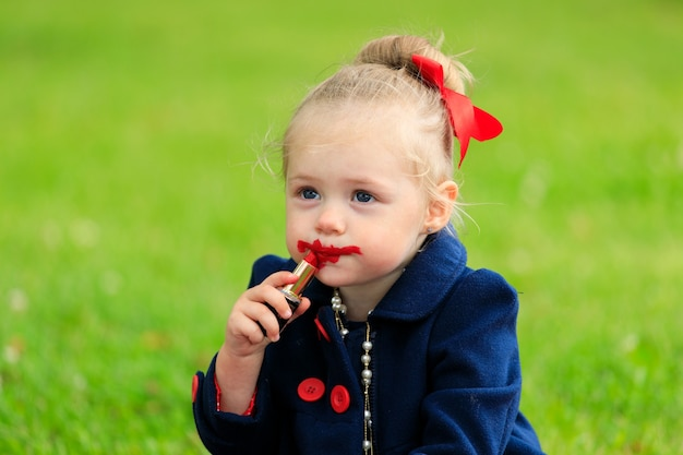 子供は座って口紅で唇を塗ります
