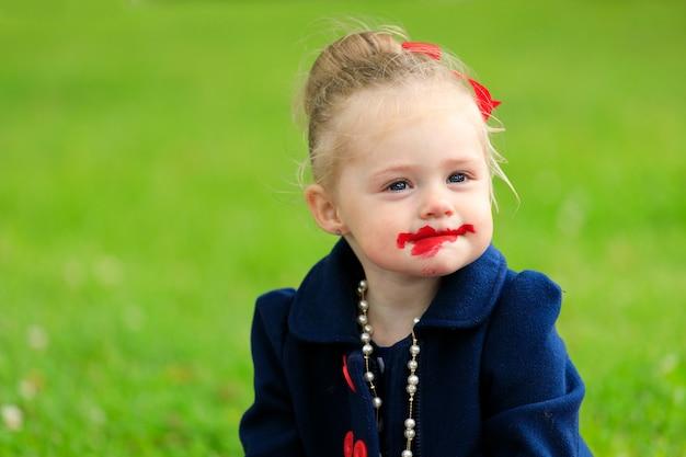 아이가 앉아서 립스틱으로 입술을 칠합니다.