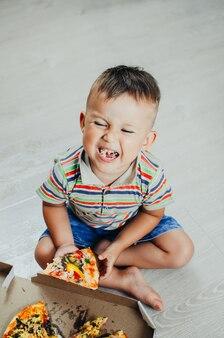 子供は床に座って、ショートパンツとtシャツで非常に食欲をそそる貪欲なピザを食べます