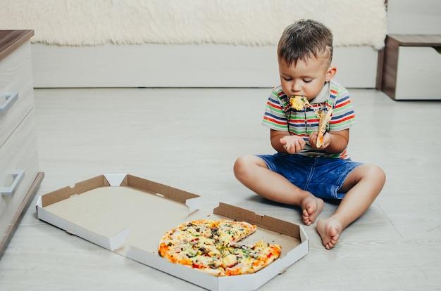 子供は床に座って、非常に食欲をそそる貪欲なピザをショートパンツとtシャツで食べます
