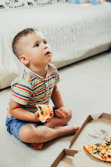 아이는 바닥에 앉아서 반바지와 티셔츠를 입고 매우 식욕을 돋우고 탐욕스러운 피자를 먹습니다.