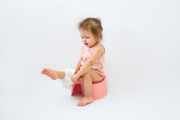 아이는 변기에 앉아 팬티를 입습니다.