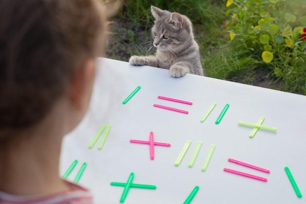 Ребенок сидит на улице и раскладывает на столе разноцветные счетные палочки.
