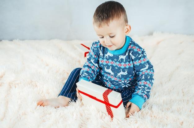 Ребенок сидит на кровати и играет с упакованными подарками, новогодняя ночь в свитере с оленями.