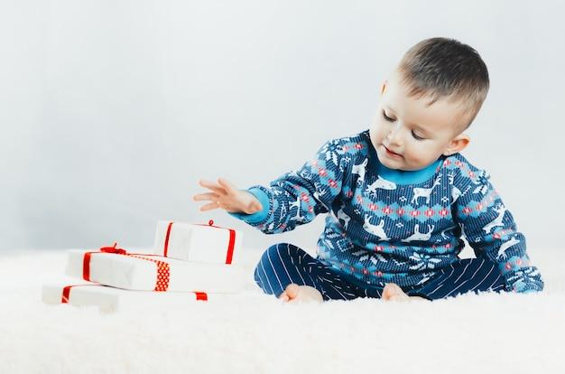 ベッドに座って、トナカイのセーターで大晦日、パックされたギフトで遊ぶ子供