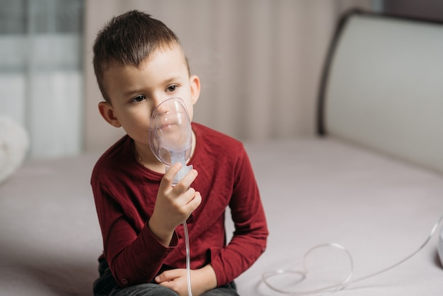 寝室のベッドに座っている子供は自分で吸入します