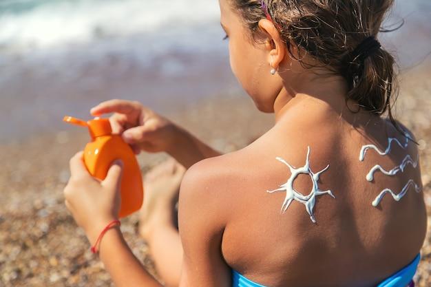 子供は背中に日焼け止めを塗ります。セレクティブフォーカス。子供。