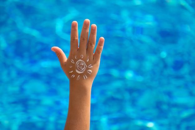 子供は手に日焼け止めを塗ります。セレクティブフォーカス。キッド。