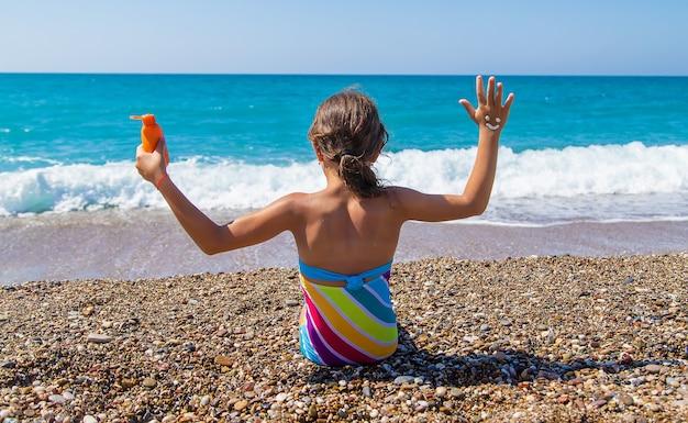 子供は手に日焼け止めを塗ります。セレクティブフォーカス。子供。
