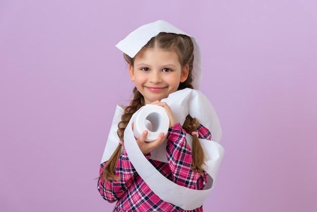 子供は微笑んで柔らかいトイレットペーパーを手に持っています。