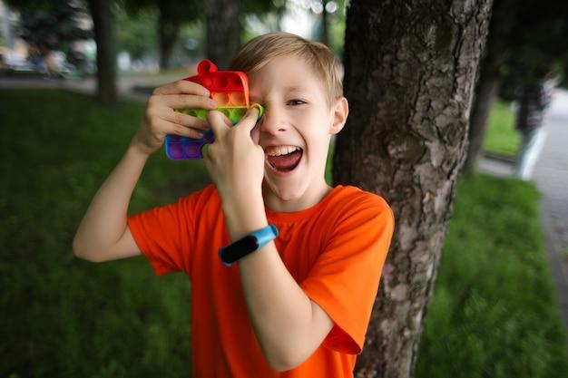 Ребенок стоит спиной к дереву и подносит глазам силиконовую антистрессовую игрушку, весело смеется