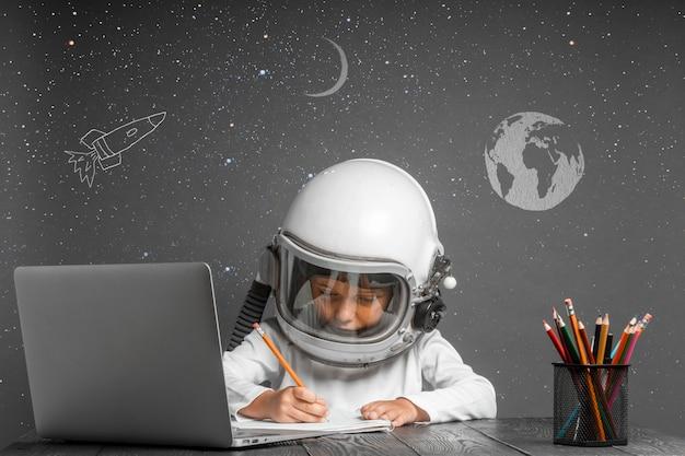 그 아이는 우주 비행사의 헬멧을 쓰고 학교에서 원격으로 공부합니다. 학교로 돌아가다