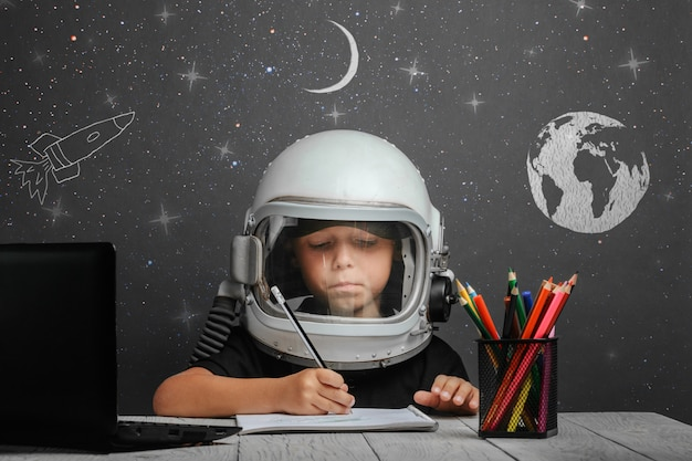 子供は宇宙飛行士のヘルメットをかぶって、学校で遠隔学習します。学校に戻る