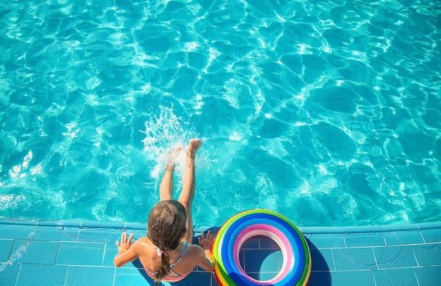 子供はプールで泳いだりダイビングしたりします。セレクティブフォーカス。自然。
