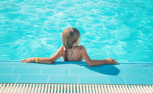 子供はプールで泳いだりダイビングしたりします。セレクティブフォーカス。自然。 Premium写真