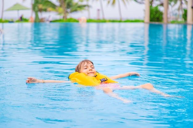 아이는 여름에 수영장에서 수영합니다. 선택적 초점.
