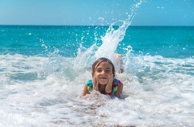 子供は波に乗って海で泳ぎます。セレクティブフォーカス。子供。