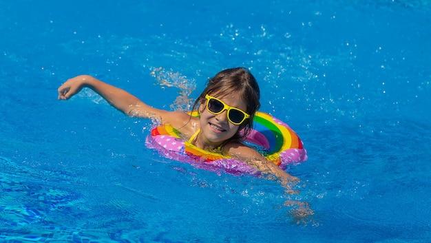 子供はプールで輪になって泳ぎます。セレクティブフォーカス。キッド。